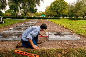 Nam Van Nguyen checks one of the refurbished memorials at the priests' burial section to ensure that is it properly aligned with one of the adjacent markers at the section south of the main outdoor altar at Calvary Catholic Cemetery.