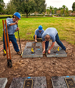 Calvary Catholic Cemetery employees, Nam Van Nguyen, Jorge Cruz and Fred Furchi, complete alingment of one of the grave markers in the priests' burial section south of the outdoor altar.