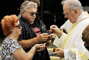Bishop Robert N. Lynch distributes the Eucharist to the faithful during the Memorial Day Mass at Calvary Catholic Cemetery on May 28.