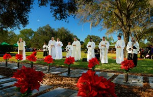 Msgr. Morris, center, leads a prayer for the repose of the souls of priests who served the diocese and who are laid to rest adjacent to the outdoor altar.