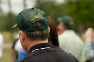 Msgr. Baver sports one of the trademark green, John Deere caps as he listens to a presentation by representatives of the John Deere company.