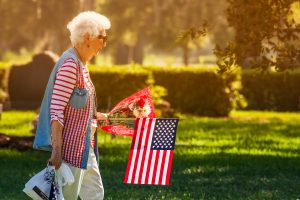 Mary Brady came from Holiday on this Memorial Day to visit and honor her husband's grave with fresh flowers and an American Flag and attend Mass. John Brady served in the Armor Branch of the United States Army.