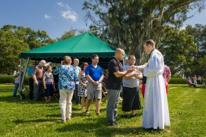 Msgr. David Toups distributes the Blessed Sacrament at Mass on Memorial Day at Calvary Catholic Cemetery, Clearwater, Fla.