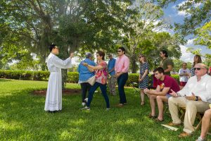 In the shade of a stately oak tree, the faithful receive Communion from Father Viet Nguyen at Mass on Memorial Day at Calvary Catholic Cemetery, Clearwater, Fla.