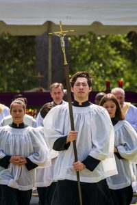 Cross Bearer, Noah Saliado, leads the recessional at the conclusion of Mass on Memorial Day.