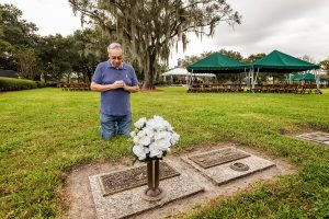 Deacon Torres prays at the grave of his deceased wife.