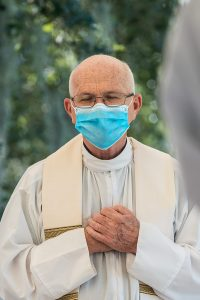 Father Arthur Proulx closes his eyes as he listens to the Opening Prayer at Mass.