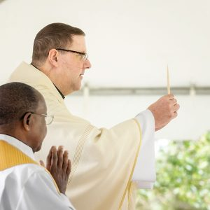 Bishop Parkes raised the Blessed Sacrament after consecration as Father Hugh Chikawe, Chaplain at Calvary, and Msgr. Robert Morris, VG, look on.
